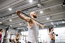 Junger Mann trainiert mit Fitnessband im Fitnessstudio