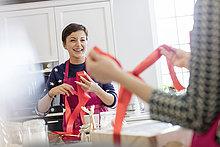 Lächelnde Catererinnen verpacken Backwaren in Schachteln mit rotem Band in der Küche