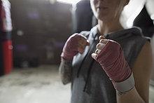 Boxerin mit eingewickelten Handgelenken in Kampfstellung im Fitnessstudio