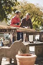 Seniorenfrau schneidet Holzbohle mit Säge, während sie mit dem Mann im Hof arbeitet.