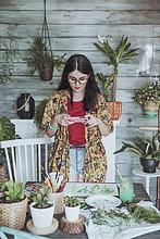 Junge Frau malt Pflanzen mit Aquarellen