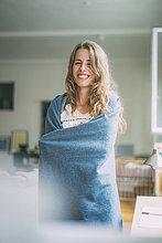 Fröhliche junge Frau zu Hause in eine Decke gehüllt