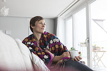 Porträt einer Frau, die sich bei einer Tasse Kaffee zu Hause entspannen möchte.