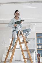 Junge Frau in ihrer neuen Wohnung sitzt auf einer Leiter und hält eine elektrische Bohrmaschine.