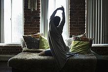 Rückansicht der Frau, die sich zu Hause auf dem Bett ausstreckt