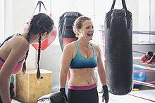 Lachende Boxerinnen neben Boxsäcken im Fitnessstudio