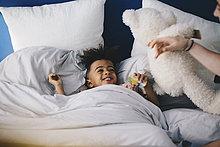 Lächelnder Junge schaut Mutter an, während er zu Hause auf dem Bett liegt.
