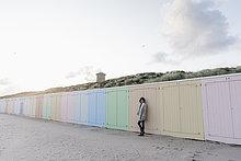 Frau lehnt an Strandhütte