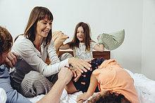 Eltern und ihre Kinder bei einer Kissenschlacht im Bett