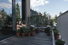 Lächelnde Frau entspannt auf dem Balkon, umgeben von Pflanzen