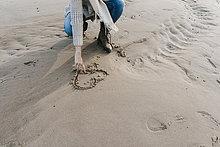 Frau kauert am Strand und zeichnet ein Herz im Sand.