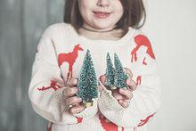 Kleines Mädchen mit Miniatur-Weihnachtsbaum, Nahaufnahme