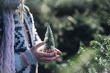 Kleines Mädchen hält einen Spielzeug-Weihnachtsbaum, Nahaufnahme