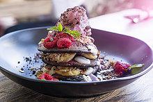 Dekoriertes rosa Dessert mit Himbeer- und Minzblättern