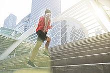 Mann in rotem Fitness-Hemd, der in der Stadt oben läuft