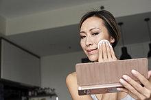 Frau zu Hause mit Handspiegel entfernen Make-up mit Wattepad