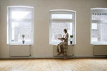Reife Frau im leeren Raum mit Laptop am Fenster