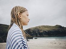 Seitenansicht des blonden Mädchens, eingewickelt in ein gestreiftes blaues Handtuch am Strand gegen den Himmel.