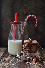 Herzförmige Lebkuchenplätzchen auf Deko-Schlitten und eine Flasche Milch