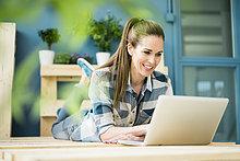 Lachende Frau mit Laptop in der neuen Wohnung