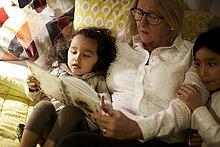 Hochwinkelansicht von Großmutter Lesebuch zu Enkelinnen im Liegen zu Hause