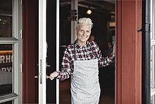 Porträt eines lächelnden, selbstbewussten Handwerkers am Eingang des Restaurants