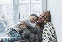 Lächelnde junge Mutter hält den Sohn am Fensterbrett zu Hause.