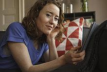 Porträt einer selbstbewussten Frau mit digitalem Tablett auf dem Sofa zu Hause