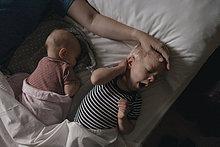 Vater liegt neben seiner Tochter und seinem Sohn im Bett.