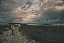 Frankreich, Bretagne, Landeda, Dunes de Sainte-Marguerite, junge Frau steht in der Düne bei Dämmerung